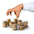 Hand greift nach Euromünzenstapeln