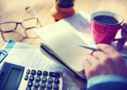 Geschäftsmann bei Abrechnung mit Notebuch und Taschenrechner