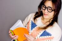 Studentin mit Brille liest in einem Buch.