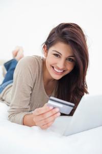 Lachende junge Frau auf Bett hält Kreditkarte in der Hand.