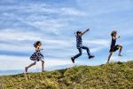 Kinder laufen hintereinander auf einen Berg.