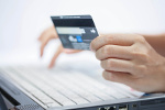 Hand hält Kreditkarte während Online-Shopping