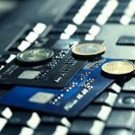 Kreditkarten und Münzen liegen auf Tastatur