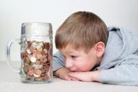 Kleiner Junge schaut auf Bierglas voller Geldmünzen