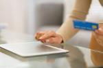 junge Frau tippt auf ihrem Tablet mit Kreditkarte in der Hand